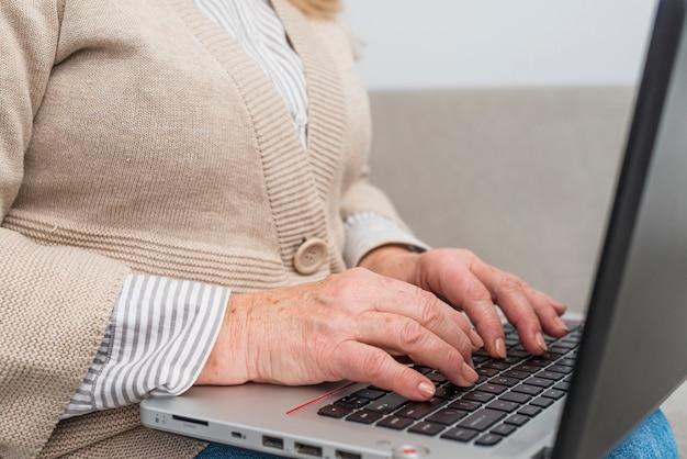 Close-up van de hand van de hogere vrouw het typen op digitale tablet