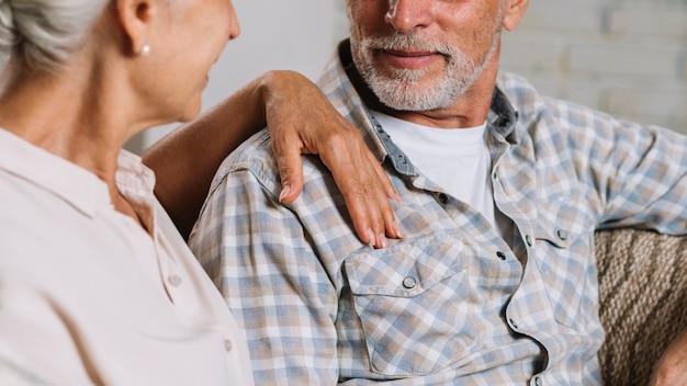 Close-up van de hand van de hogere vrouw op de schouder van haar echtgenoot