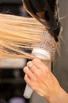 Close-up van de hand van de kapper is het drogen van haar van de blonde jonge vrouw in een kapsalon