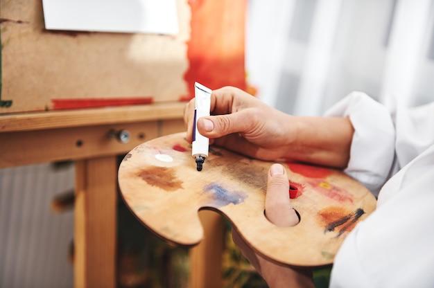 Close-up van de hand van de kunstenaar die de donkerblauwe olieverf uit de buis in het palet in een voorkant van een ezel knijpt