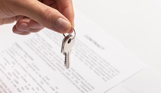 Close-up van de hand van de man met een sleutel van een nieuw appartement boven tafel met contract