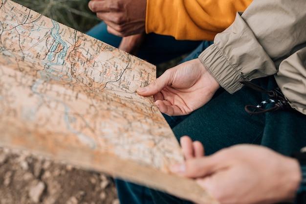 Close-up van de hand van de mannelijke wandelaar die de kaart houdt
