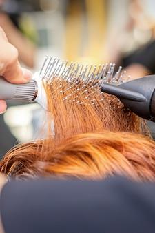 Close-up van de hand van de meester met föhnen en haarborstel die vrouwelijk rood haar blaast in een salon