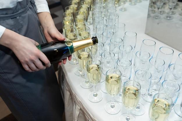 Close-up van de hand van de ober gieten champagne in glazen