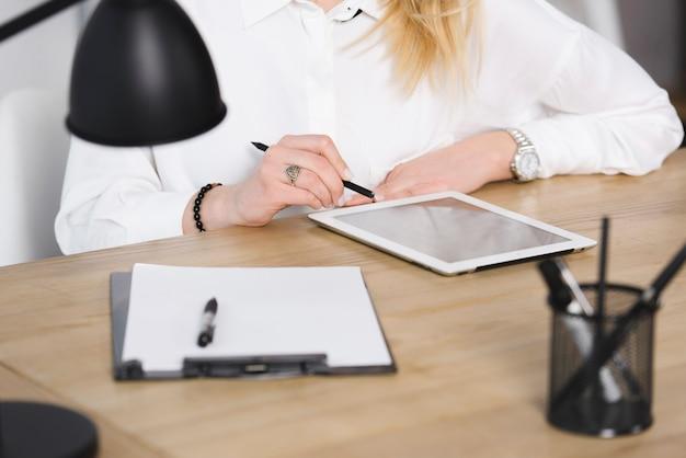 Close-up van de hand van de onderneemster die digitale tablet op houten over het houten bureau gebruiken