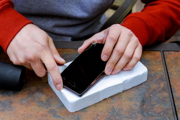 Close-up van de hand van de persoon die het beschadigde scherm op mobiele telefoon bevestigt
