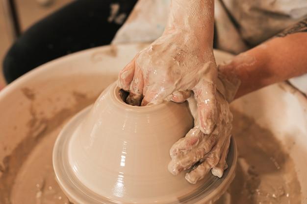 Close-up van de hand van de pottenbakker die tot een aarden kruik op de cirkel leidt