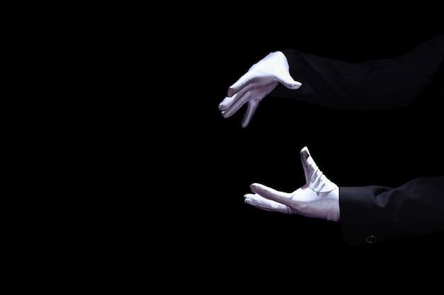 Close-up van de hand van de tovenaar die witte handschoen draagt tegen zwarte achtergrond