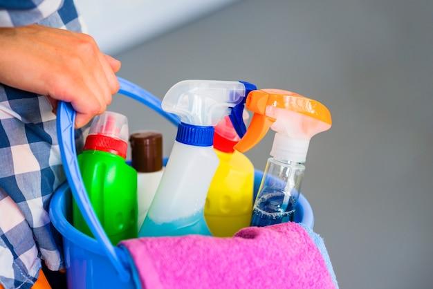 Close-up van de hand van de vrouw die blauwe emmer met het schoonmaken van apparatuur houdt