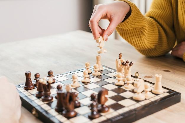 Close-up van de hand van de vrouw die de raad van het schaakspel op houten bureau speelt