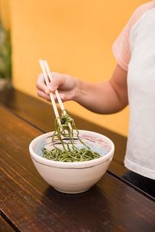 Close-up van de hand van de vrouw die groene zeewiersalade met eetstokje op houten lijst houdt