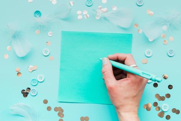 Close-up van de hand van de vrouw die op papier met pen schrijft die met veer wordt omringd; pailletten en knop op groenblauw achtergrond