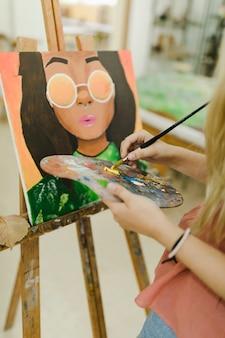 Close-up van de hand van de vrouw het schilderen op ezel met borstel