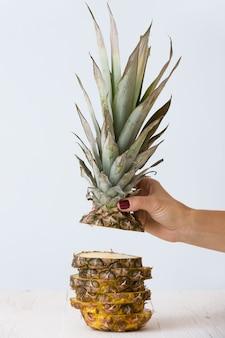 Close-up van de hand van de vrouw met gesneden ananas