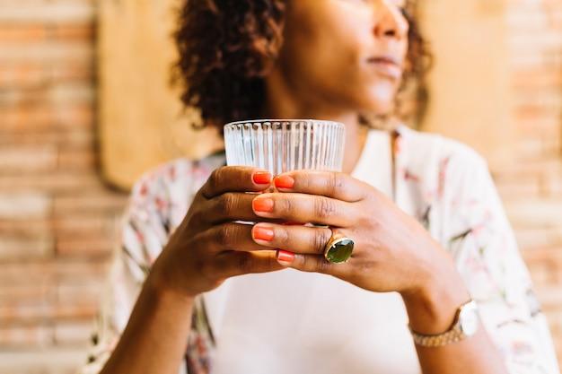 Close-up van de hand van de vrouw met glas in de hand
