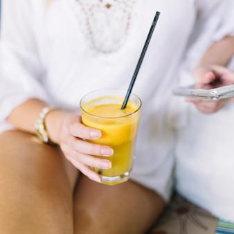 Close-up van de hand van de vrouw met glas sap met behulp van de mobiele telefoon