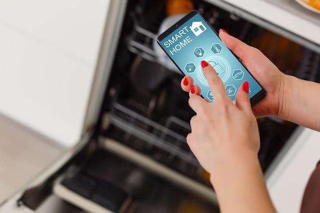 Close-up van de hand van de vrouw met vaatwasser-app op mobiele telefoon in de keuken