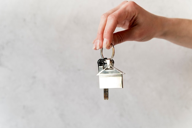 Close-up van de hand van de vrouw met zilveren huis sleutelhanger tegen betonnen muur