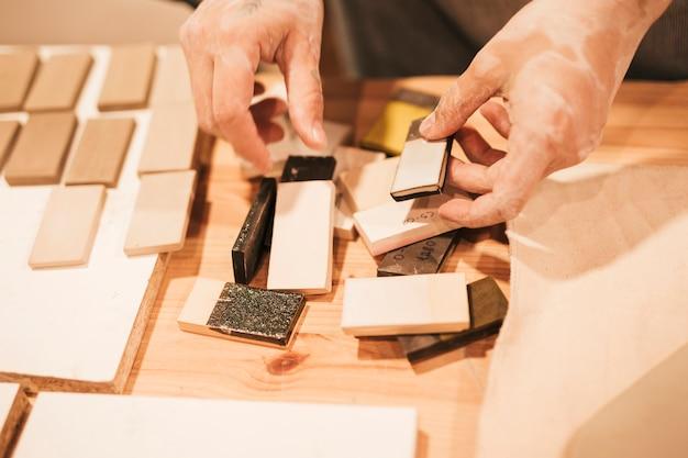 Close-up van de hand van de vrouwelijke pottenbakker die met keramische tegels op lijst werkt