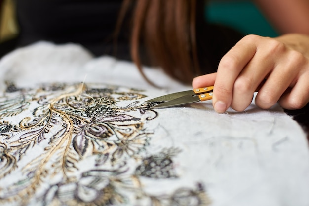 Close-up van de hand van de vrouwenarbeider die korte losse eindjes wegknippen