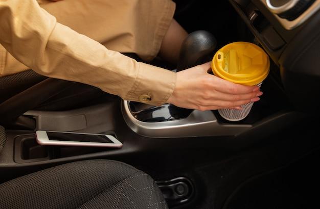 Close-up van de hand van de vrouwenbestuurder die een kop warme drank houdt tijdens het besturen van een auto.