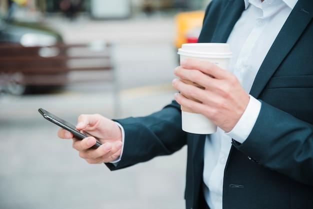 Close-up van de hand van de zakenman die meeneemkoffiekop houdt die mobiele telefoon met behulp van
