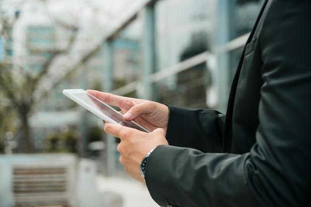 Close-up van de hand van de zakenman met behulp van de mobiele telefoon in de open lucht