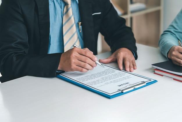 Close-up van de hand van de zakenmaneigenaar die een pen vasthoudt om het cv op kantoor te controleren.