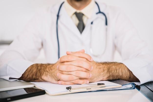Close-up van de hand van een arts op het klembord