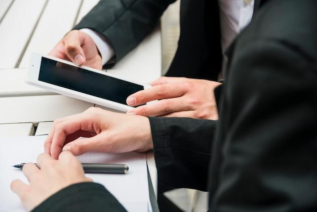 Close-up van de hand van een bedrijfsmensen met mobiele telefoon; pen en document op tafel