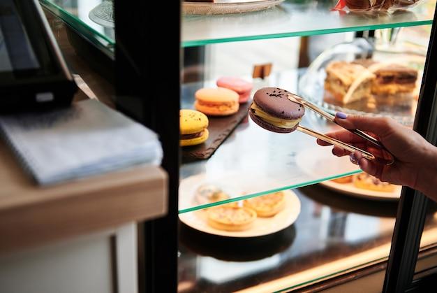 Close-up van de hand van een cafetariamedewerker die een macaron selecteert uit een cafetaria-vitrine