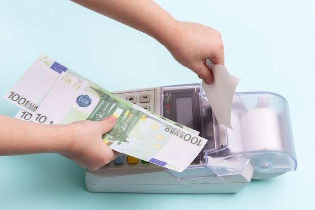 Close-up van de hand van een kind die een blanco kassiercheque van de terminal scheurt en een hand met enkele honderden eurobankbiljetten op een blauwe achtergrond, bovenaanzicht, kopieerruimte. betaling voor winkelconcept