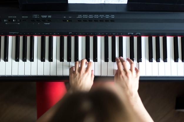Close-up van de hand van een klassieke musicus die piano of elektronische synthesizer speelt (pianotoetsenbord)
