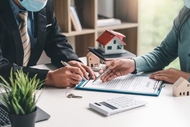Close-up van de hand van een makelaar die wijst op een document dat een koopovereenkomst voor een huis ondertekent op kantoor.