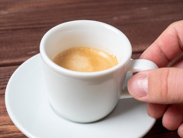 Close-up van de hand van een man die een klein wit kopje aromatische espresso vasthoudt op een witte schotel.