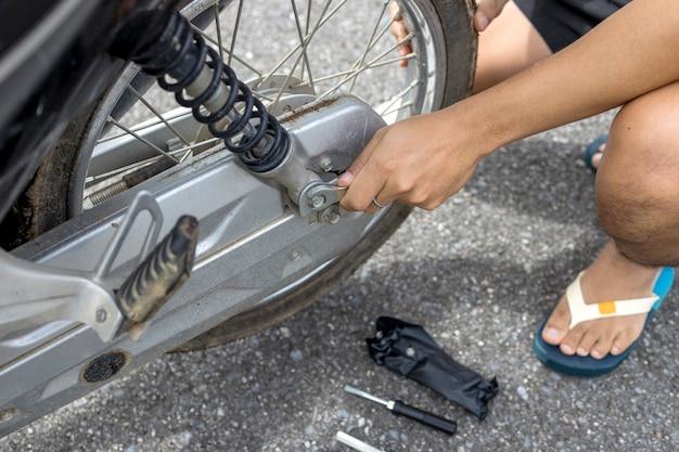 Close-up van de hand van een man die een motorfiets aan de kant van de weg repareert.