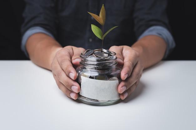 Close up van de hand van een man met een glazen pot met een munt binnen en een boom op de munt