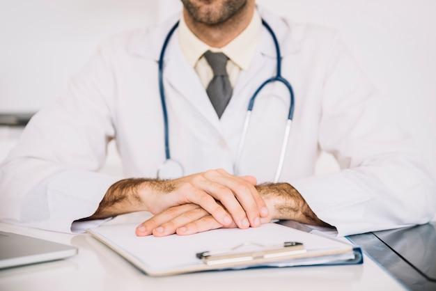Close-up van de hand van een mannelijke arts met klembord op bureau