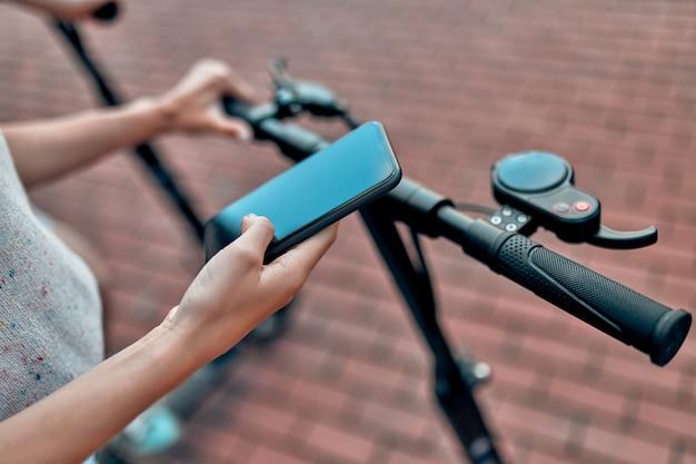 Close-up van de hand van een meisje dat haar smartphone gebruikt en op een elektrische scooter rijdt.
