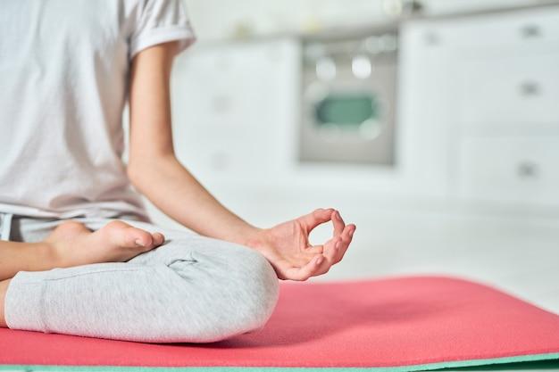 Close-up van de hand van een ontspannen hispanic tienermeisje in sportkleding die yoga beoefent, mediteren op een mat in de keuken. home interieur achtergrond. gezonde levensstijl, ontspanningsconcept