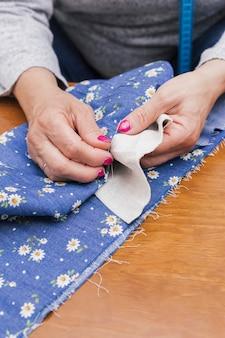 Close-up van de hand van een persoon die de bloemenstof met naalden op bureau naait