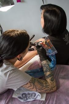 Close-up van de hand van een tattoo-meester in zwarte handschoenen met een tattoo-machine maakt een tattoo volgens de schets