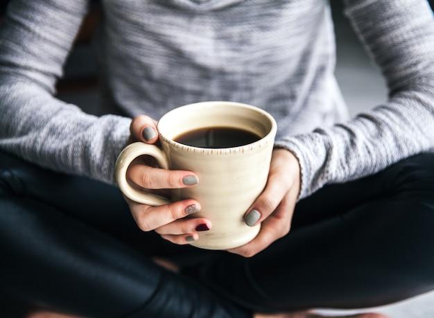 Close-up van de hand van een vrouw die een kop hete koffie houdt. mode, vrije tijd