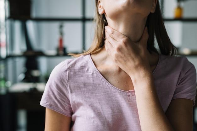 Close-up van de hand van een vrouw die haar hals raakt
