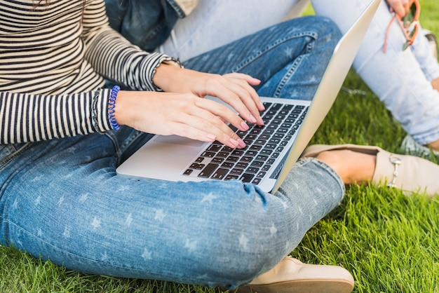 Close-up van de hand van een vrouw die laptop in park met behulp van