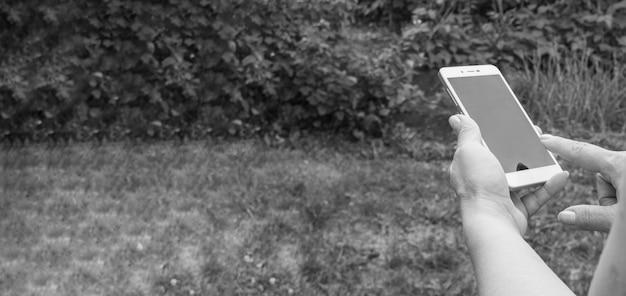 Close-up van de hand van een vrouw, met behulp van een smartphone om een bericht te verzenden in de tuin, buiten, zwart-wit, banner