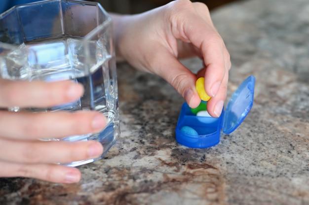 Close-up van de hand van een vrouw met een glas water dat geneeskunde neemt. pillen in een doos.