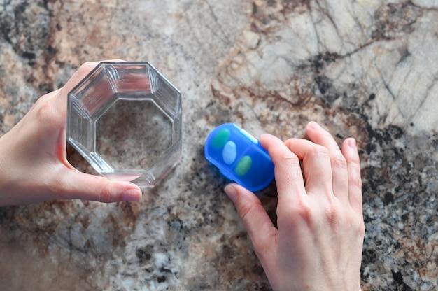 Close-up van de hand van een vrouw met een glas water dat geneeskunde neemt