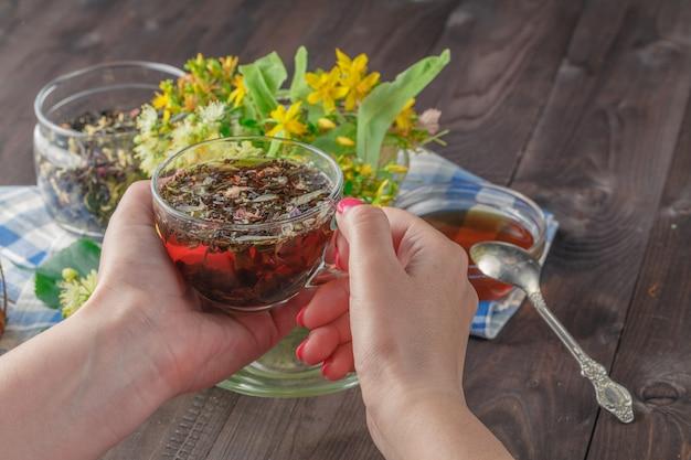 Close-up van de hand van een vrouw met een kopje honing thee met honing