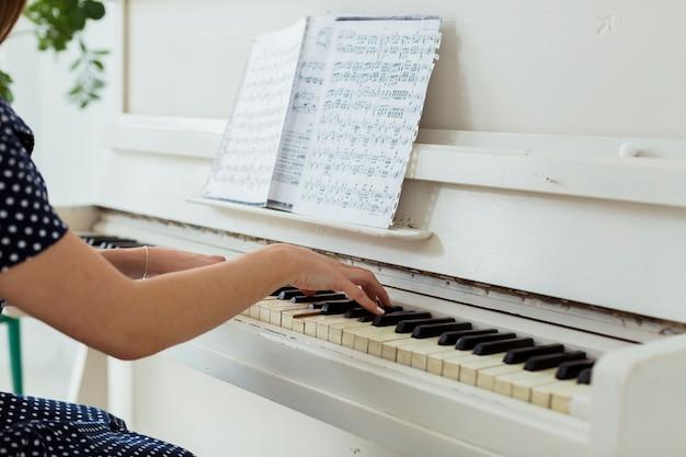 Close-up van de hand van een wijfje die de piano speelt